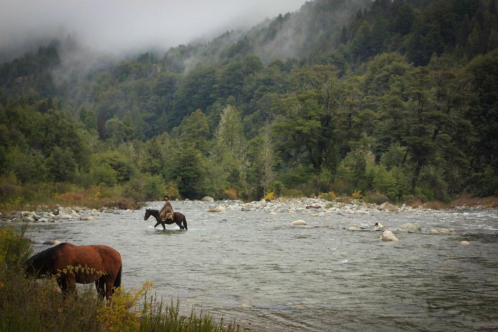 Gaucho crossing the Rio Azul. Comarca Andina. Argentina.