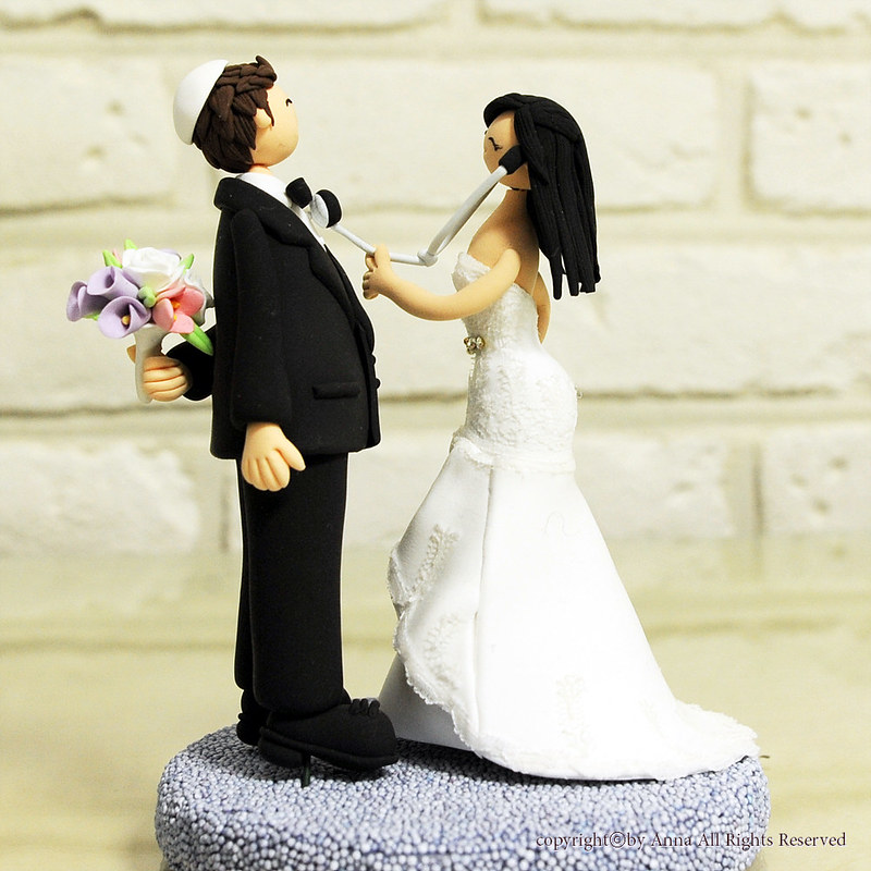 Noivinhos de topo de bolo com noiva médica ou enfermeira e estetoscópio e noivo judeu com quipá
