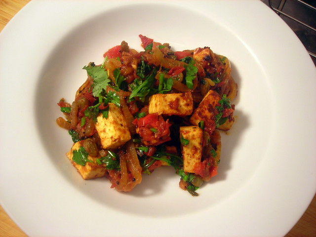 Fried paneer cheese, with spiced tomato sauce and green Persian raisins