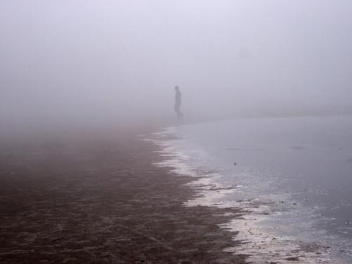 man walking the foggy shoreline at Stroomi beach, Tallinn, Estonia