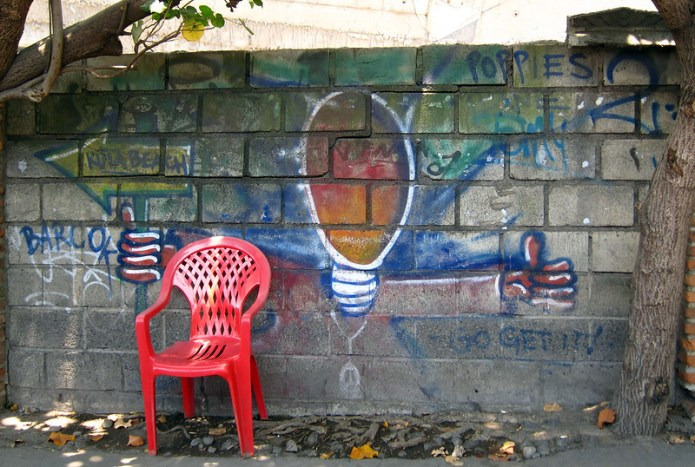 graffiti and red plastic chair
