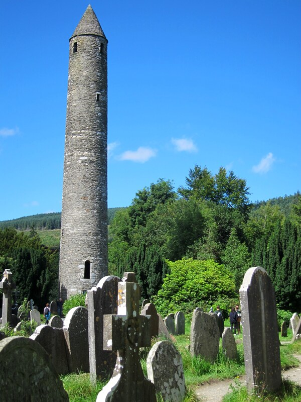 Gorgeous clear blue sky and very green trees. In the foreground are various gravestones and crosses; in the background is a tall stone round tower, jutting far above the ground.