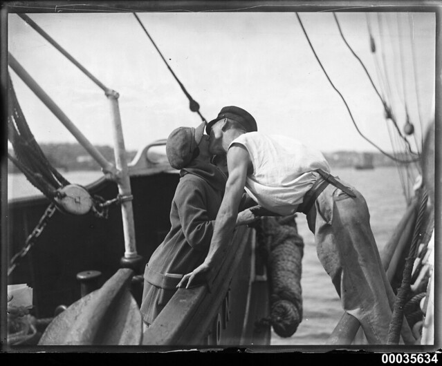 Man and woman kissing across two vessels, 1920-1939