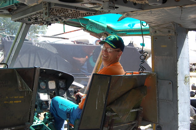 Mike wearing his cover from his time on the USS Theodore Roosevelt  and his UT Orange shirt (required for the fall Saturdays) sits in a helicopter seat