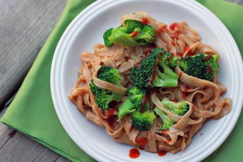 Top-down view of a white dish with wide rice noodles, broccoli, peanut sauce, and a drizzle of sriracha.