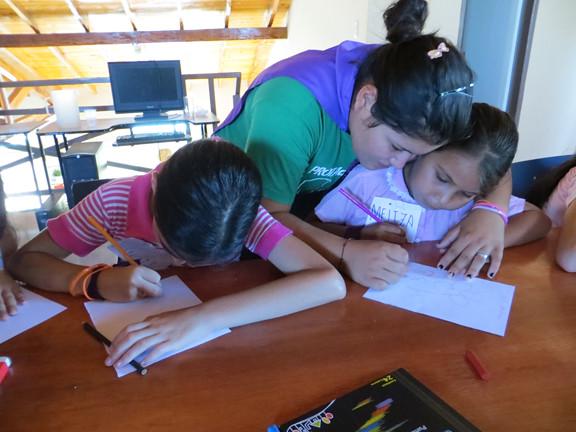 Luz helps Meliza with a self-esteem activity