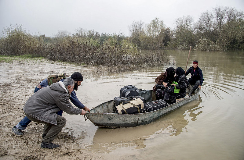 Rebel fighters launch a boat carrying two Syrian women fleeing across the Orontes River to Turkey near the northern Syrian town of Darkush.  Photo courtesy of Freedom House flickr.com/photos/syriafreedom/8311300394