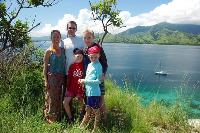 family boat mountains ocean Indonesia