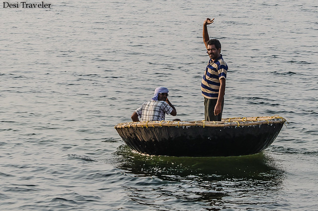 man standing and waving in a coracle made of bamboo