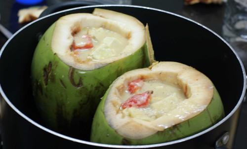 Paneer in Tender coconut shells being simmered in water bath