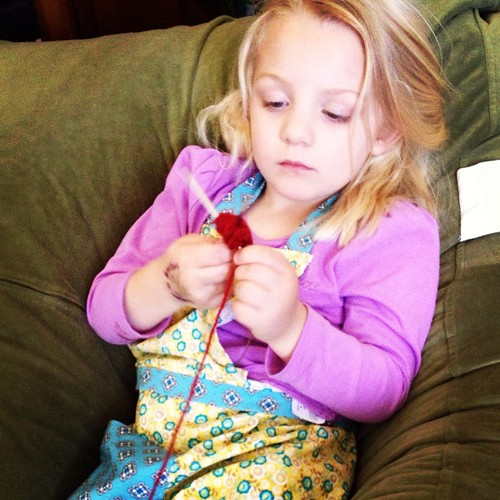 """Alice """"knitting"""" a hat."""