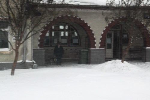 Stationmaster at Pufeşti takes shelter beneath the verandah, while watching our train pass