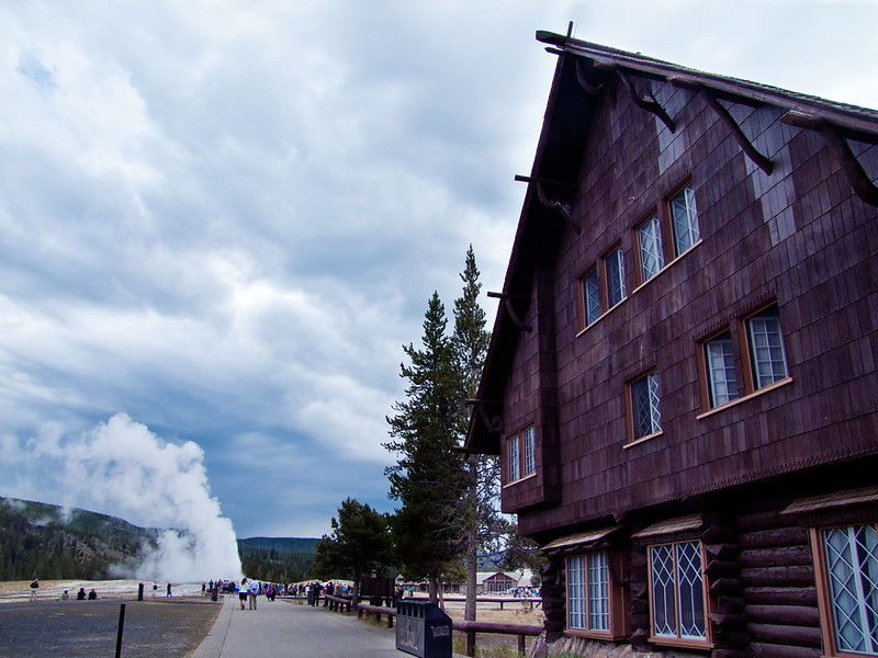 Old Faithful Inn, with Old Faithful Geyser erupting in distance