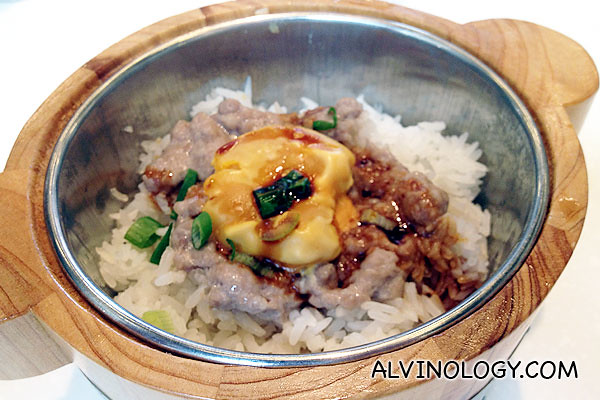 Rice served in a small wood pot with salted egg and minced meat