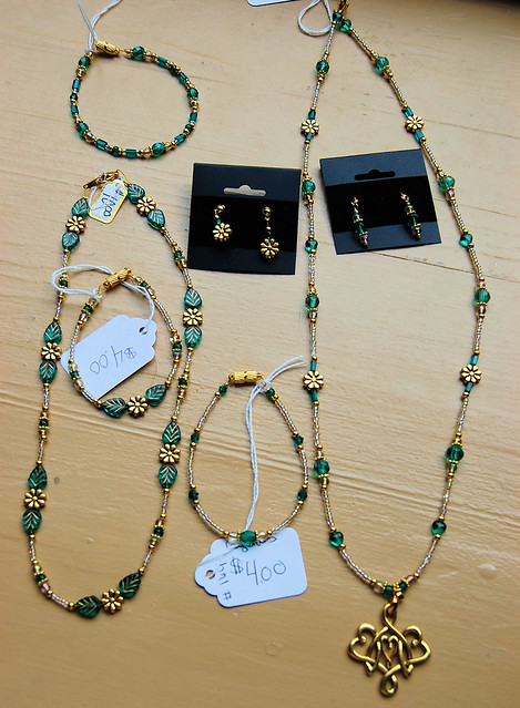 A collection of necklaces, earrings, and bracelets featuring gold tones with Aquagreen  glass