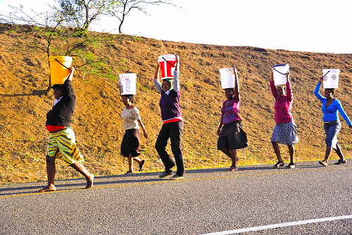 a team of zulu girls carrying water in buckets on their heads