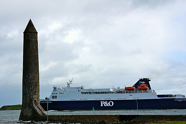 A ferry passes Chaine Memorial Tower near Larne Harbour