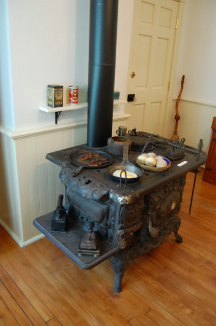 Cook's domain with a large iron stove preparing breakfast on top and warming clothes irons on the side