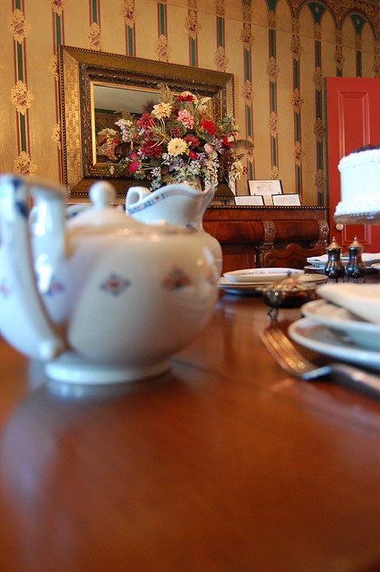 Tea pot is in foreground looking across plate setting on a cherry wood table to large flower arrangement sitting on sidebar across the room