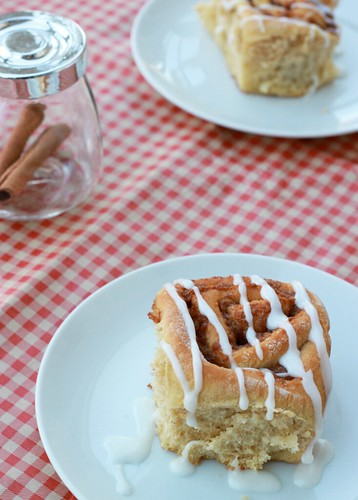 In the foreground is a small white plate with a tall cinnamon roll dripping with white icing. In the middle background is a small glass jar filled with cinnamon sticks, and in the far background is another plate with another roll on it.