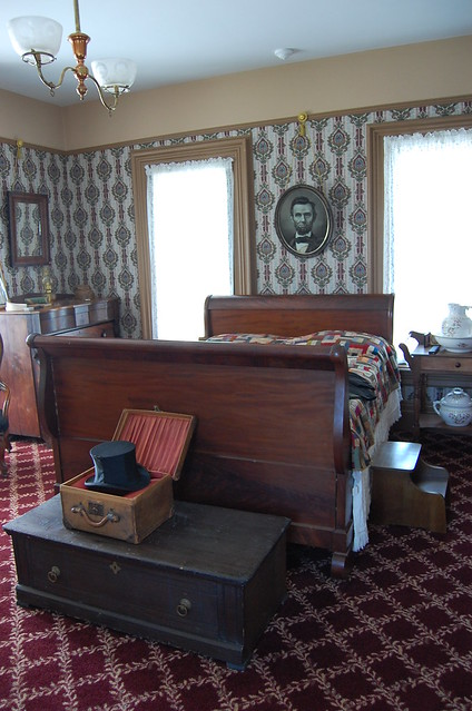 a walnut sleigh style bed with a handmade quilt over it and an oval framed print of Lincoln hanging above the head board at the foot is a travel trunk with a black tall hat