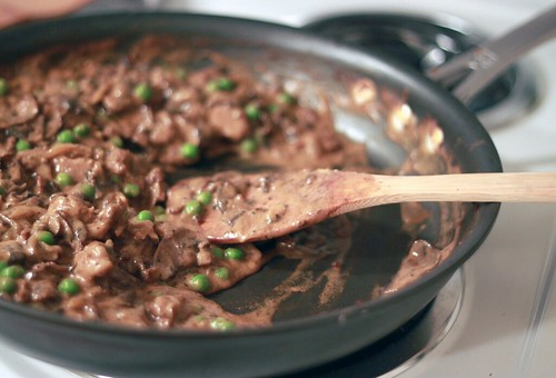 Nonstick pan filled with a dark sauce that features mushrooms, seitan, and peas.