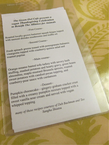 Top-down view of a small white laminated piece of paper with the Thanksgiving menu on it.