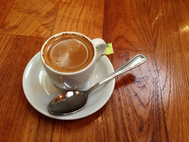 Small cup with a frothy espresso and a silver spoon.