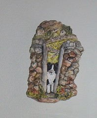 """We call this guy """"Alf"""" - it's a James Herriot plaster wall hanging showing a border collie going thru a stile in a stone wall in Yorkshire - it's been hanging in our stairway area since 1987. I don't remember ever dusting it. Ugh."""