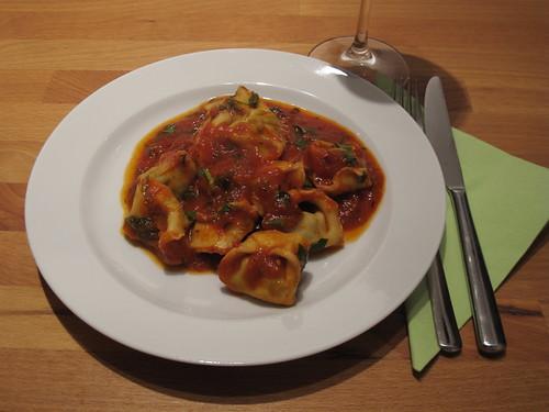 Mit Blattspinat und Ziegenkäse gefüllte Tortellini in Tomatensoße