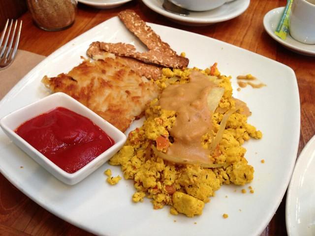 Plate of tofu scramble, ketchup, potatoes, and tempeh bacon.