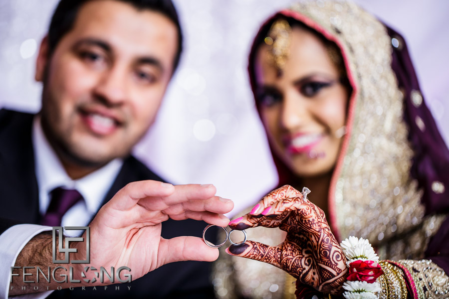 Indian bride and groom holding rings to the camera for creative photo