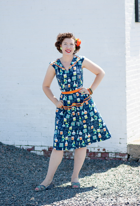 Science themed novelty print retro dress handmade from Advance 7757 in the style of a Swirl dress. Orange, lime green, and teal pop against the navy background.