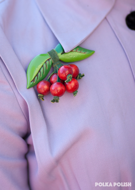A vintage cherry brooch in red and green painted wood and leather stands out on the bodice of a light purple dress
