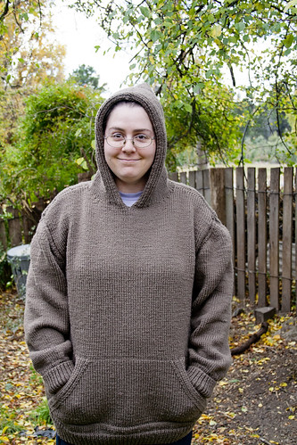 Photo of Ruth wearing the knitted jumper, taken front on with the hood up. You can see the kangaroo pocket on the front