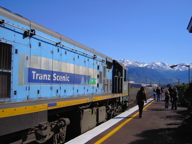 Kaikoura. Tranz Scenic train engine in Kaikoura railway station on way from Christchurch to Picton New Zealand. Snow covered mountains oen side fo station and the beach the other.