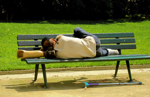 A man takes a nap on a bench while using his prosthetic leg as a pillow in Paris, France. Photo by Tricia Brooks / Special to Xpress