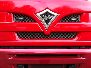 Close-up of front grill of red lorry.