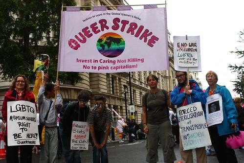 Personer med banderoll 'Queer strike' och olika plakat. Säg till om du vill ha hjälp att läsa plakattexterna.