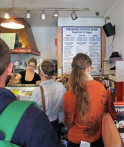 Interior of a small building - to the right is a sign with lists of baked potato toppings; to the left is the counter and a waitress, along with some toaster ovens in the background. In the foreground are lots of people waiting!