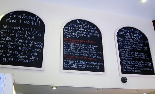three big chalkboard y signs that describe blazing salads philosophy