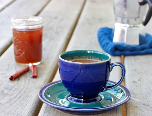 A small blue teacup on a matching blue saucer in the foreground. In the background on the left is the jar of syrup; in the right is a small metal stovetop coffeepot.