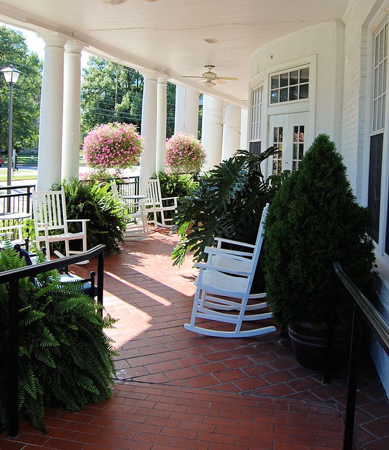 brick porch with white rockers and lovely potted plants.