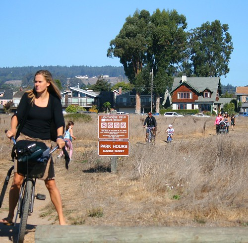 People bike and walk to West Cliff Drive across Lighthouse Field