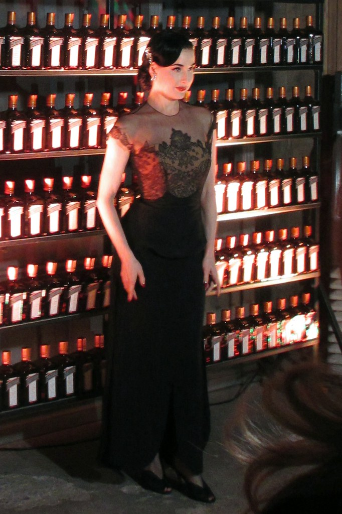 Dita von Teese poses for photos against a backdrop of Cointreau bottles.