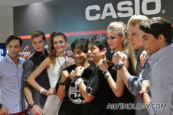 Two Casio senior staff in black tees in the middle together with the models