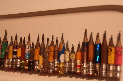 The artist carved the alphabet into the tips of these pencils using a sewing needle and razor