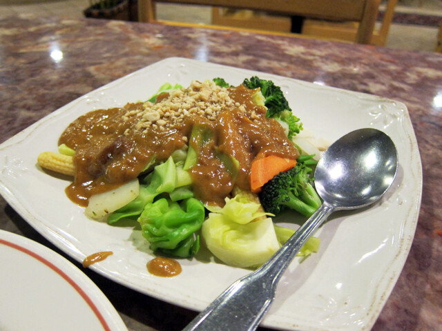 White plate with lots of green veggies and peanut sauce.