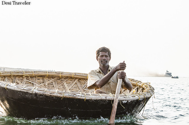 a boatman poses for picture in his coracle or round boat