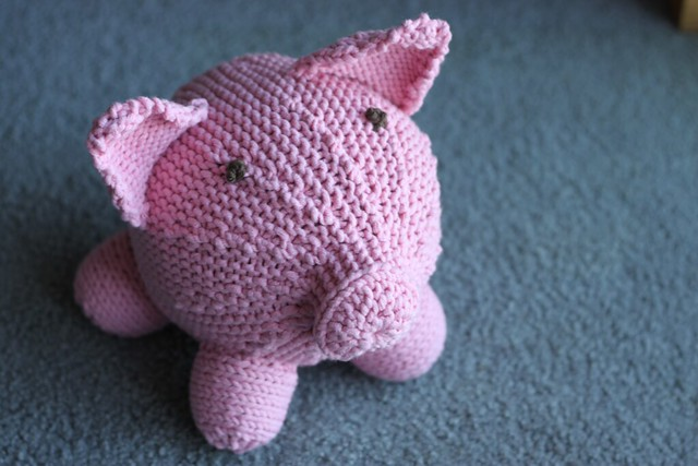 Round knitted pink pig with big triangle ears.